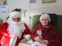 Bessie U. is all smiles as Santa delivers a gift.